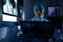 Vista frontal de una joven cirujana de raza mixta examinando rayos X en quirófano en el hospital. El cirujano usa bata quirúrgica, gorra, guantes de látex y máscara. - foto de stock