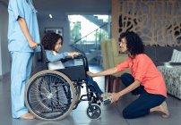 Вид збоку змішаної раси мати втішний її інвалідів сина в холі в лікарні. — стокове фото