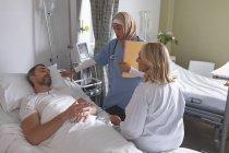 Seitenansicht verschiedener Ärztinnen, die mit kaukasischen männlichen Patienten auf der Station im Krankenhaus interagieren — Stockfoto