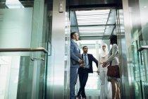 Visão de baixo ângulo de diversos empresários usando elevador no escritório moderno — Fotografia de Stock
