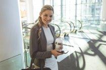 Vista laterale della felice donna d'affari che guarda la fotocamera in un moderno edificio per uffici — Foto stock