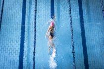 Високий кут зору кавказька жінка носить купальник і рожеві шапки робити Фрістайл інсульт в басейні — стокове фото