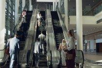 Vista frontal de diversos empresários usando escadas rolantes no escritório moderno — Fotografia de Stock