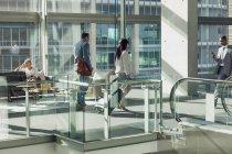 Вид сбоку на разношерстных бизнесменов, гуляющих в современном офисе — стоковое фото