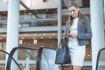 Vista frontal da bela empresária usando telefone celular perto da escada rolante em um prédio de escritórios moderno — Fotografia de Stock