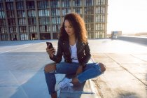 Front view of a young African-American woman wearing a leather jacket while sitting and using a mobile phone on a rooftop with a view of a building and the sunlight — Stock Photo