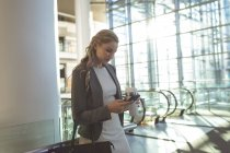 Side view of beautiful businesswoman using mobile phone and holding disposable coffee cup in a modern office building — Stock Photo