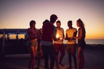 Front view of group of diverse friends lighting sparklers near cameraman during sunset — Stock Photo