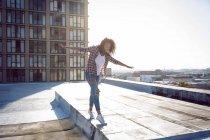 Vista frontale di una giovane donna afro-americana che indossa una giacca a quadri con le mani tese mentre cammina su un tetto con vista su un edificio e luce solare — Foto stock