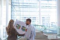 Vue arrière de gens d'affaires discutant sur le plan dans un immeuble de bureaux moderne — Photo de stock