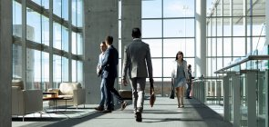 Rear view of businessman walking down the hallway in modern office — Stock Photo