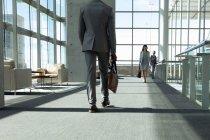 Вид сзади на бизнесмена, идущего по коридору в современном офисе — стоковое фото