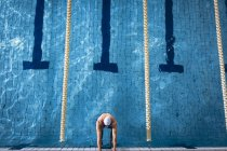 High angle view of male Caucasian swimmer wearing a white swimming cap and goggles holding on the side of the swimming pool — Stock Photo