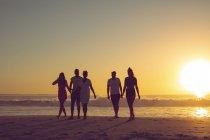 Vista frontal de diversos amigos caminhando juntos na praia durante o pôr do sol — Fotografia de Stock