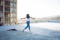 Вид сзади на молодую афроамериканку с протянутыми руками, бегущую по крыше с видом на здание и солнечный свет — стоковое фото