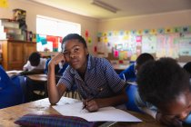 Front view close up of a young African schoolgirl leaning on her desk and looking up while writing in her notebook during a lesson in a township elementary school classroom, in the background her classmates are also writing in their books — Stock Photo