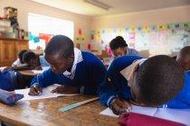 Фронтальный вид двух молодых африканских школьников, пишущих в тетрадях во время урока в школьном классе, на заднем плане их одноклассники тоже пишут в своих книгах — стоковое фото