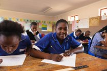 Portrait close up of a young African schoolgirl leaning on her desk, looking to camera and smiling while writing in her notebook during a lesson in a township elementary school classroom. — Stock Photo