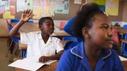 Front view of a young African schoolboy sitting at his desk, raising his hand to answer a question during a lesson in a township elementary school classroom, in the foreground a schoolgirl is listening attentively — Stock Photo