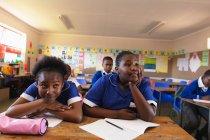 Vista frontale da vicino di due giovani studentesse africane appoggiate alla scrivania, che alzano lo sguardo e ascoltano durante una lezione in una classe di una scuola elementare cittadina, sullo sfondo le compagne di classe ascoltano e scrivono nei loro libri — Foto stock