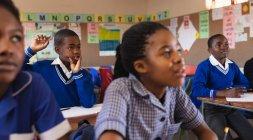 Vista dianteira de um estudante Africano novo que senta-se em sua mesa, levantando sua mão para responder a uma pergunta durante uma lição em uma sala de aula da escola elementar do Township, em torno dele os colegas estão sentando-se em suas mesas e escutando atentamente — Fotografia de Stock