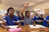Vue de face de deux jeunes écolières africaines assises à leur bureau, l'une levant la main pour répondre à une question lors d'une leçon dans une classe de l'école élémentaire d'un canton, en arrière-plan leurs camarades de classe écoutent attentivement — Photo de stock