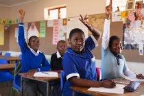 Nahaufnahme einer Gruppe junger afrikanischer Schüler, die an ihren Schreibtischen sitzen und die Hände heben, um eine Frage während einer Schulstunde in einer Township-Grundschule zu beantworten — Stockfoto