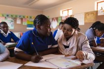 Close up front view of a middle aged African female school teacher squatting down and helping a young African schoolgirl sitting at her desk during a lesson in a township elementary school classroom. — Stock Photo