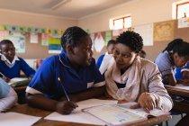 Vista da vicino di un'insegnante di scuola femminile africana di mezza età accovacciata e che aiuta una giovane studentessa africana seduta alla scrivania durante una lezione in una classe della scuola elementare cittadina . — Foto stock