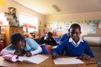 Front view close up of a young African schoolgirl sitting at her desk writing in her book and a young African schoolboy sitting beside her looking down and thinking during a lesson — Stock Photo