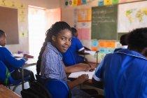 Vista lateral de cerca de una joven colegiala africana sentada en su escritorio y dando la vuelta, mirando a la cámara y sonriendo durante una lección en un aula de la escuela primaria del municipio. - foto de stock