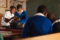 Vista frontal de dois jovens estudantes africanos olhando para um smartphone durante uma pausa das aulas em uma sala de aula da escola primária da cidade, em primeiro plano a visão traseira de dois outros meninos também olhando para algo juntos — Fotografia de Stock