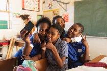 Фронтальный вид группы молодых африканских школьниц, весело позирующих и делающих селфи со смартфоном во время перерыва с уроков в школьном классе. — стоковое фото
