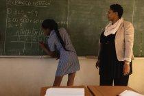Veduta posteriore di una giovane studentessa africana in piedi davanti alla classe che scrive sulla lavagna con la sua insegnante africana di mezza età accanto a lei che guarda, durante una lezione in una classe della scuola elementare cittadina — Foto stock