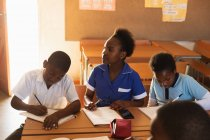 Front view of a young African schoolboy and two schoolgirls sitting at desks writing during a lesson in a township elementary school classroom, one schoolgirl is looking up to the blackboard — Stock Photo