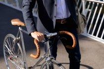 Vista laterale metà sezione di uomo a piedi e ruote la sua bicicletta in città. Nomade digitale in movimento . — Foto stock