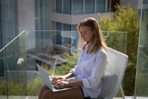 Side view of a young Caucasian woman wearing a white shirt, sitting on a chair on a balcony using a laptop, building and trees in the background. — Stock Photo