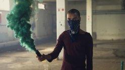 Вид спереди человека с полузакрытым лицом в длинных рукавах и с дымовой трубкой, производящей зеленый дым внутри пустого склада — стоковое фото