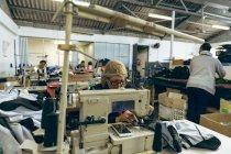 Передній погляд на кавказьку жінку середніх років, яка сидить і працює швейною машинкою на фабриці спортивного одягу, з колегами, видимими, працюючи на швейних машинах і сортуючи через тканини на задньому плані.. — стокове фото