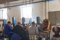 Vue arrière d'un groupe diversifié de trois ouvriers assis et actionnant des machines dans une usine fabriquant des balles de cricket . — Photo de stock