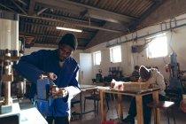Вид спереду крупним планом молодого афроамериканського людини, що працює машина в майстерні на заводі, що робить крикет куль, на задньому плані афро-американський чоловік колега сидить на Workbench працює на іншій частині виробничої лінії. — стокове фото