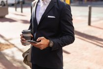 Front view mid section of man wearing a jacket using his smartphone and holding a takeaway coffee, standing on a city street. Digital Nomad on the go. — Stock Photo
