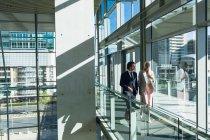 Зовнішній вигляд ділових людей взаємодіючих один з одним при ходьбі в коридорі в сучасному офісі. — стокове фото