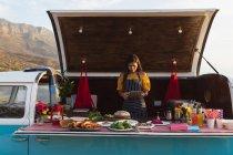 Вид спереди на молодую женщину смешанной расы с помощью планшетного компьютера, стоящего в открытом верхнем фургоне и предлагающего ассортимент еды на вынос для продажи — стоковое фото