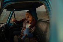 Vista lateral de una joven pareja mixta sentada en su camioneta sonriendo y abrazándose al atardecer, durante una parada en un viaje por carretera. Están sentados en los asientos delanteros y el interior del coche está iluminado con luces de cuerda . - foto de stock