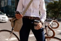 Vue de face au milieu d'un homme tenant un café à emporter et utilisant un smartphone, appuyé sur son vélo dans une rue de la ville. Nomade numérique en mouvement . — Photo de stock