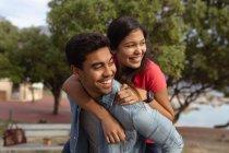 Вид спереди на улыбающуюся молодую смешанную расовую пару, весело сидящую на солнце и отводящую взгляд в сторону, на фоне деревьев и моря — стоковое фото
