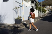 Side view of a young mixed race woman carrying a backpack crossing an urban street in the sun — Stock Photo