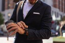 Vista frontale sezione centrale di un giovane caucasico controllare l'ora sul suo orologio e tenendo un caffè da asporto, in piedi su una strada della città. Nomade digitale in movimento . — Foto stock