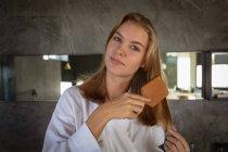 Retrato de cerca de una joven mujer caucásica usando un albornoz cepillándose el pelo, mirando directamente a la cámara en un baño moderno . - foto de stock